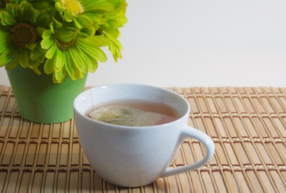 Cup of tea on bamboo mat with green