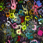 Children's colorful hand prints on black background